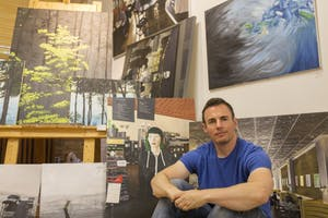 University of Minnesota alum Brendan Kramp poses beside art work he created in his studio at the Casket Art building on Sunday, July, 29. Brendan will be presenting his work at the Uptown Art Festival from August 3-5.