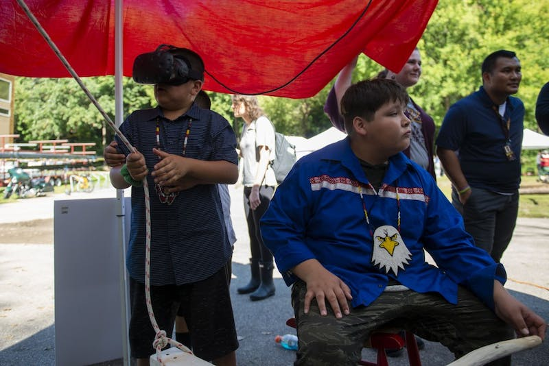 "Ganebik Johnson wears a virtual reality headset and attempts to steer a canoe at the ""Navigating Indigenous Futures"" event on Thursday, Sept. 19, 2019."