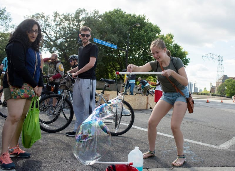 Sophomore Moretta O'Connell makes a giant bubble on Saturday during Open Streets on SE University Ave.