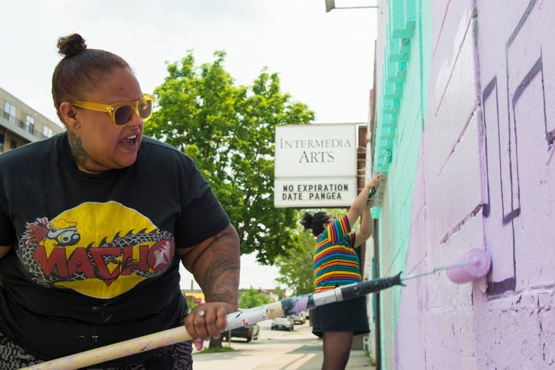 Joy Spika, left, and Leilani Mendoza paint the outer walls of Intermedia Arts in Uptown Minneapolis on Monday afternoon. The mural is part of the B-Girl Be exhibit, which opens on Saturday.