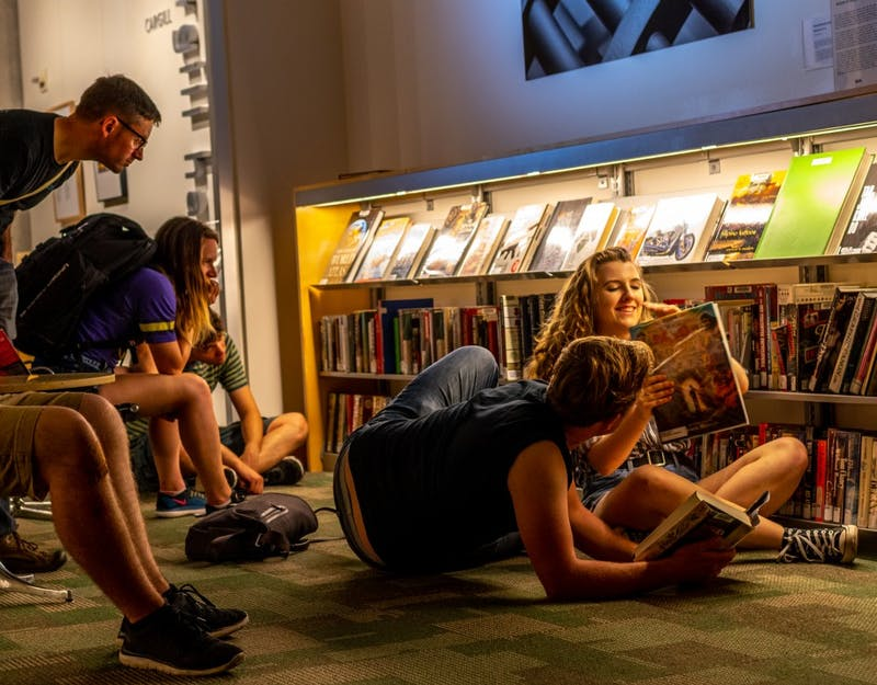 "Viewers of the exhibit, ""The Section of Disapproved Books,"" interact at the Weisman Art Museum."