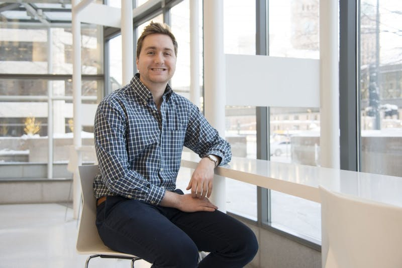 """Andrew Swisher, who graduated from the University in 2018, poses for a portrait in downtown Minneapolis on Feb. 8. Swisher created Bibliate, a website that condenses and summarizes scholarly articles that is similar to """"SparkNotes."""""""