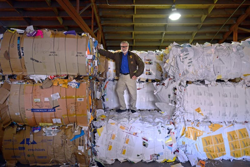 """Facilities Support Supervisor Dana Donatucci, known to many as """"The Recycling Guy,"""" poses for a portrait among bales of recycled materials on Tuesday, Nov. 7 in Minneapolis. Donatucci has been in charge of all things recycling at the University for 30 years."""