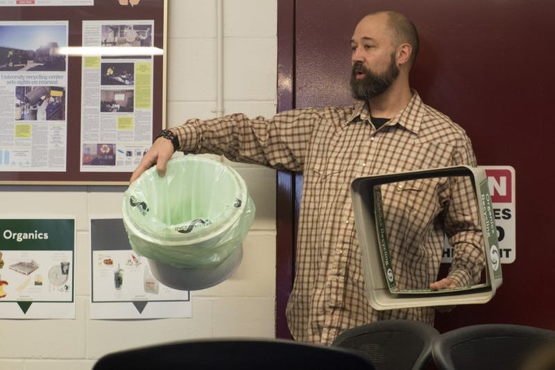 Interim Zero Waste Coordinator Todd Tanner demonstrates how the new organics bins will work on Saturday, March 2 at the Como recycling facility. The bins will be put into every building at the University.