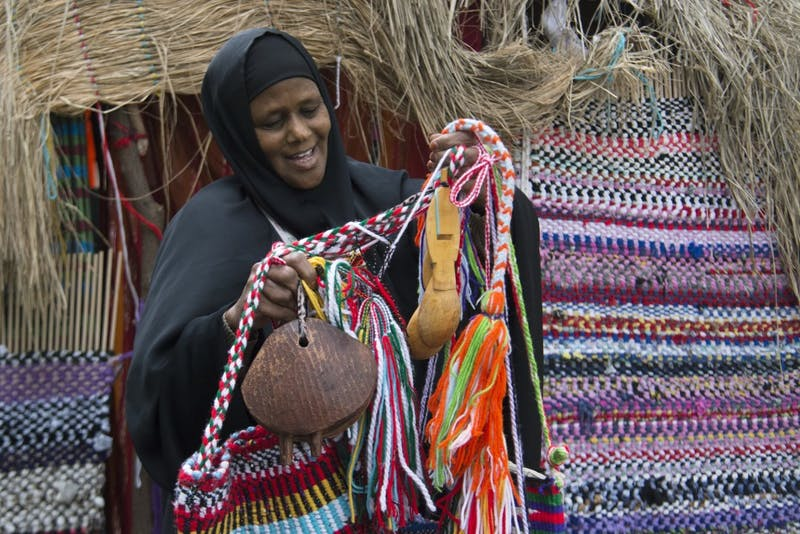 Fatuma Halki holds different types of traditional Somali weaving, camel bells and a spoon from her bag in front of the Somali House on Thursday, Sept. 27 in Minneapolis.  Halki does much of the weaving herself.