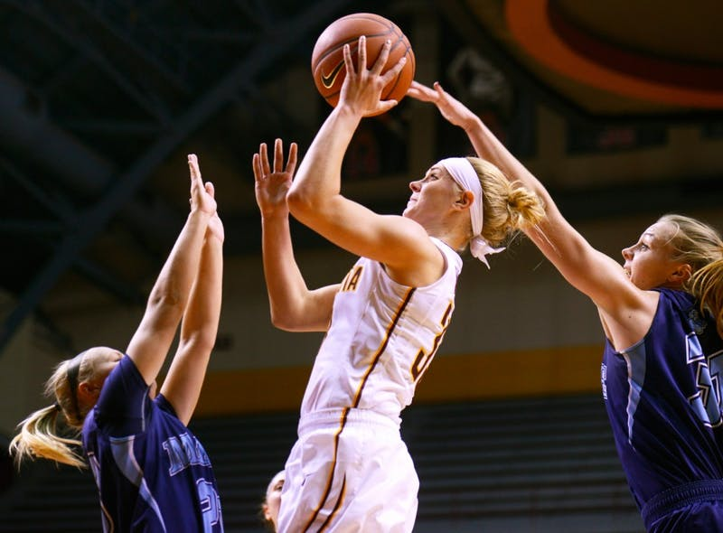 Carlie Wagner manages to shoot in between two Maine defenders at Williams Arena on Nov. 20, 2015.