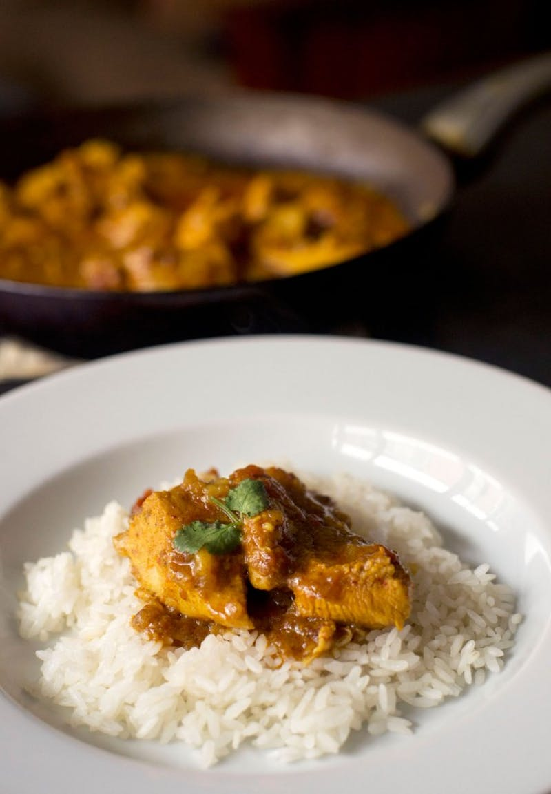 A simple chicken curry served on a bed of rice.