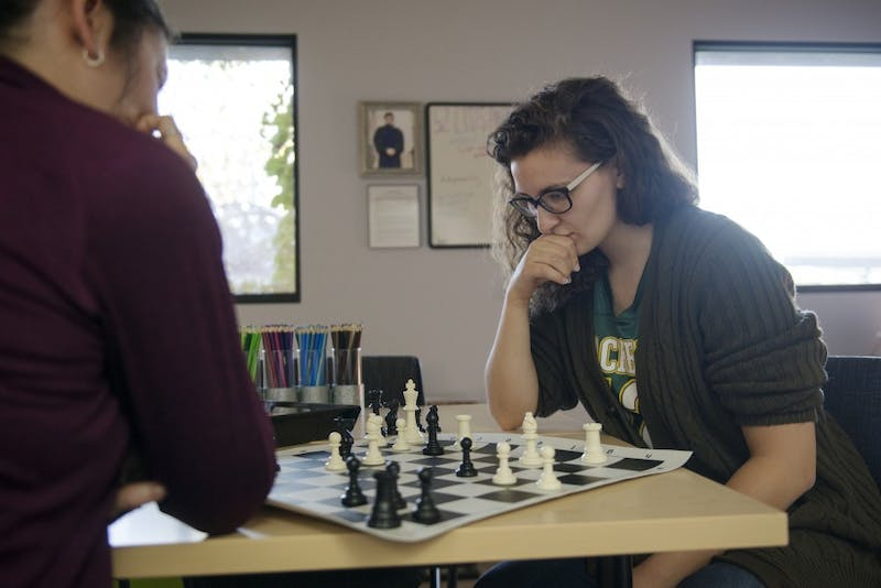 Law students Jessica Szuminski and Makenzie Krause play a game of chess on Friday, Oct. 12, in Mondale Hall. The therapy room that they are in offers law students the chance to unwind without the distractions of technology or homework.