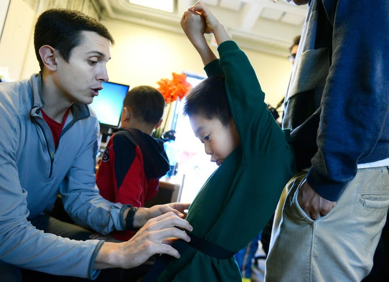 Graduate Assistant Zachary Pope adjusts helps fit 5-year-old Chris Chen with an accelerometer at Williamson Hall on Sunday. The test is for a study to help better understand how young children are affected through home-based excise gaming.