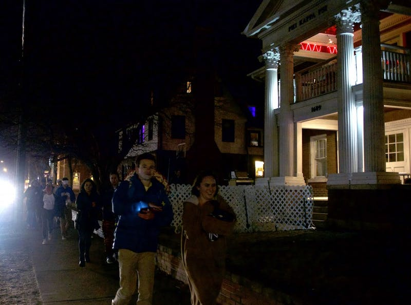 A large group walks past fraternities on Fraternity Row on March 10, 2017.