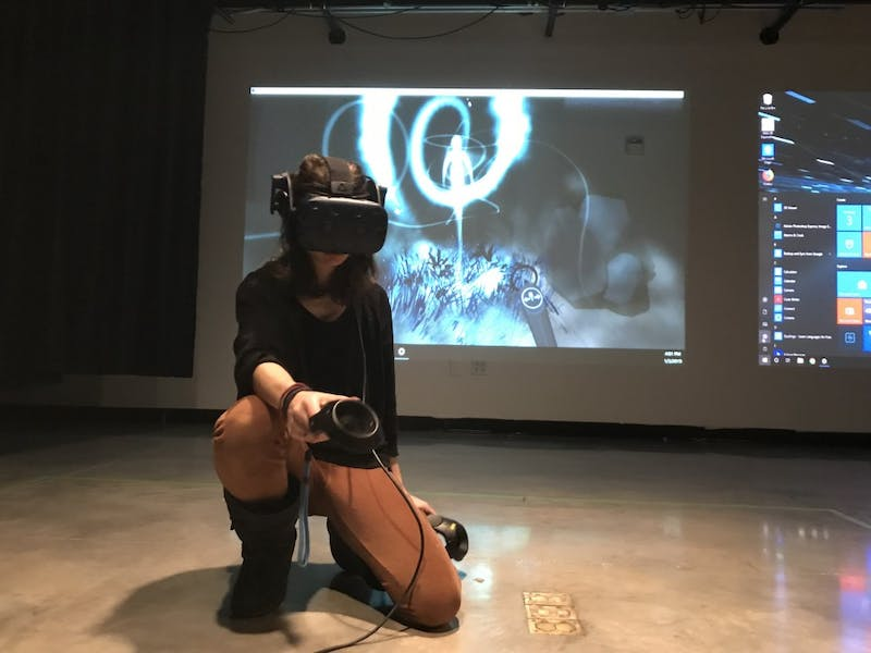 Melinda Hiller works in VR to create the drawings that are projected behind her.