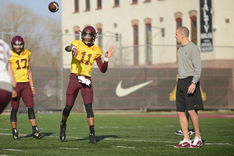 Offensive coordinator Jay Johnson, right, watches sophomore quarterback Demry Croft throw a ball in a practice on March 10, 2016.
