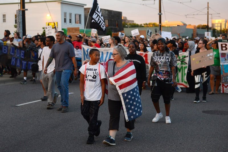 Taye Clinton, left, and Susan Montgomery walk in front of a crowd of protesters on University Avenue in St.Paul on Friday, June 16.