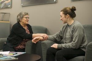 """Massage therapist Ioana """"Coca"""" Vladislav gives an impromptu hand massage to student Emily Clarke at the University Recreation and Wellness Center on Monday, Nov. 11. Vladislav is known as """"Grandma Coca"""" and has been working at the U for 20 years."""