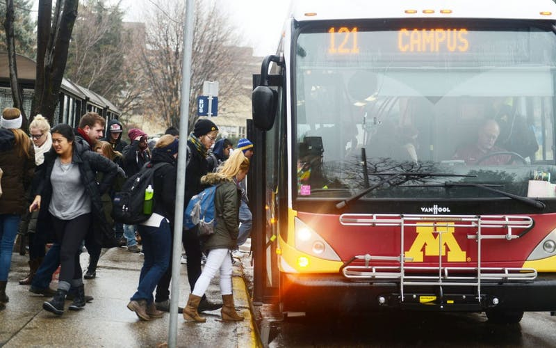 University students get on and off the campus connector bus on Tuesday.  On December 7, the campus connectors, along with other metro transit buses, will resume bus service on Washington Avenue for the first time since May 2011.