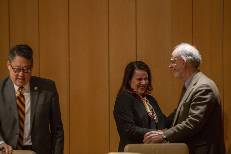 University President-designate Joan Gabel shakes the hand of Regent Ken Powell after being voted into the job on Tuesday, Dec. 18 at McNamara Alumni Center.