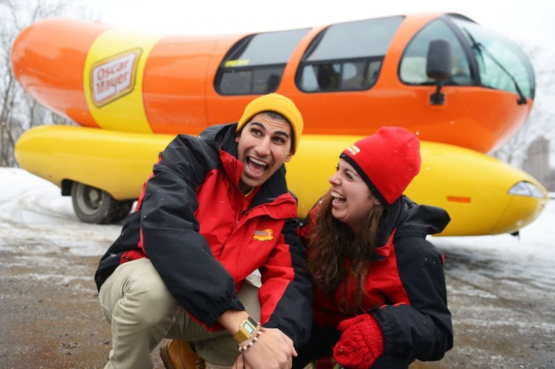 """Hotdoggers"" Joe Zerka and Alexandra Longo pose outside of their Weinermobile in Minneapolis on Monday afternoon."