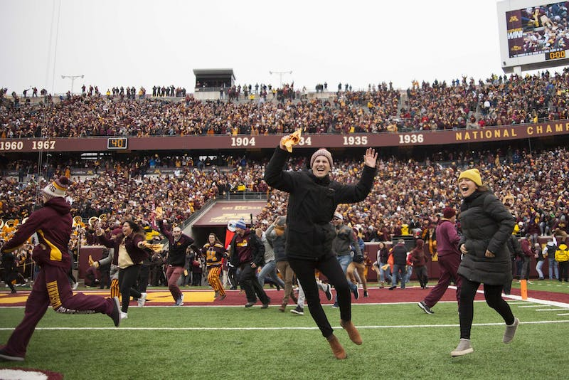 Fans rush the field at TCF Bank Stadium on Saturday, Nov. 9 following the Gophers 31-26 win over Penn State. The win brings their record to 9-0. A first since 1940.