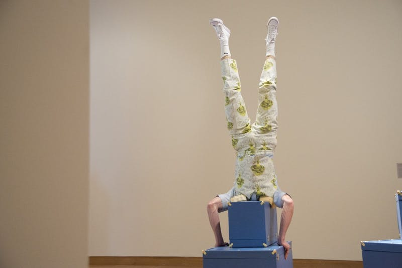 "Avery McQuaid Nelson Lawrence does a head stand as part of a performance piece on Friday, Feb. 1 at the new Weisman Art Museum exhibition ""Baggage Claims.""  The exhibition displays the work of eighteen international artists and will be on display until May 12."