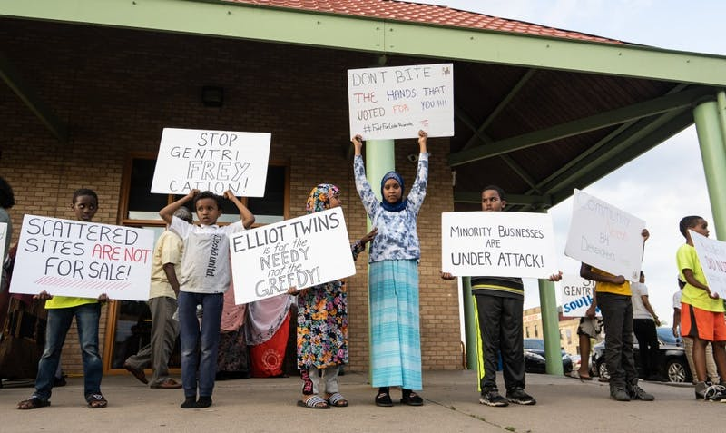 Youth hold signs protesting plans for the development of a mall in the Cedar Riverside area at a protest organized by the Somali Mothers of MN at Currie Park on Sunday, July 7.