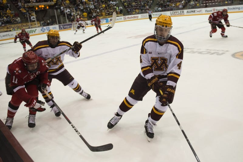 Freshman Ben Brinkman keeps the puck away from St. Lawrence on Saturday, Nov. 17 at Mariucci Arena.