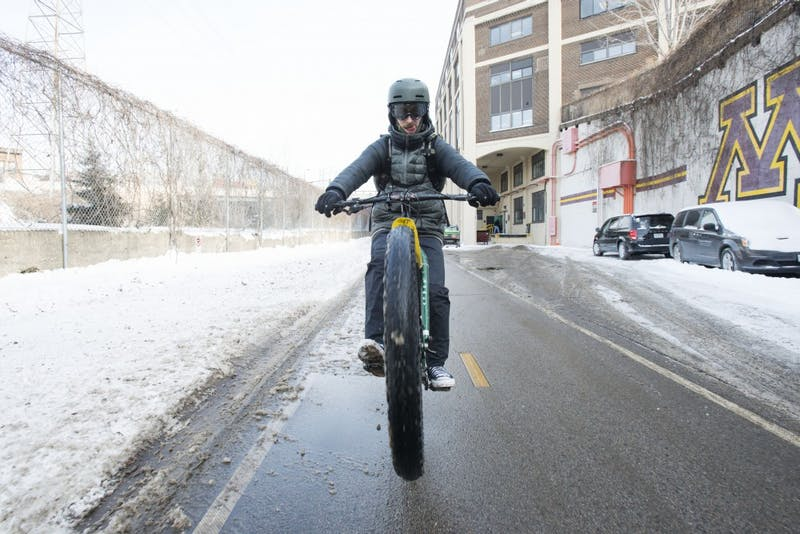 Bennett Figueroa pops a wheelie on his bike as he rides down the Dinkytown Greenway on Friday, Feb.1