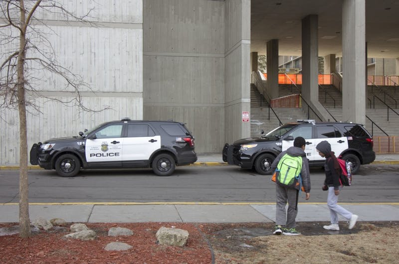 Two children walk past police cars parked outside Riverside Plaza on Monday, March 19.