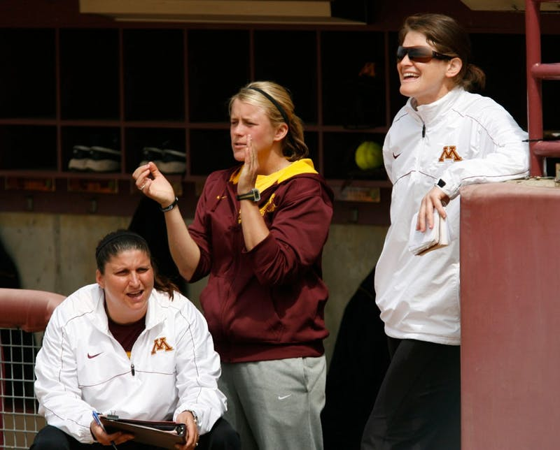 Minnesota head softball coach Jessica Allister, right, volunteer assistant Dannie Skrove and pitching coach Piper Ritter cheer from the dugout May 5, 2013, against Indiana. Allister has led the Gophers to three straight seasons with 30 or more wins since her arrival in 2010.
