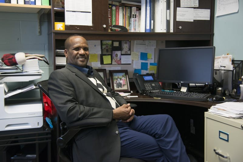Brian Coyle Center Director Amano Dube poses at his desk on Friday, Nov. 16. Dube has been the center's director for five years and says that it is like his second home.