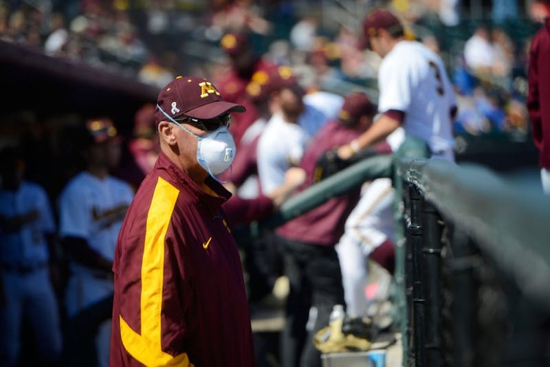 Gophers pitching coach Todd Oakes watches from the dugout as the Gophers play Michigan at Siebert Field on Sunday afternoon. Oakes' acute myeloid leukemia is in remission for the second time.