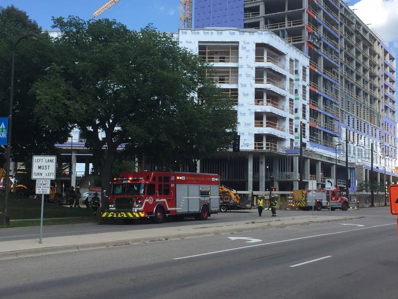 Fire trucks and first responders cordon off a stretch of University Avenue Southeast where a bulldozer ruptured a gas line Monday. Around 100 people gathered to watch as responders addressed the leak.