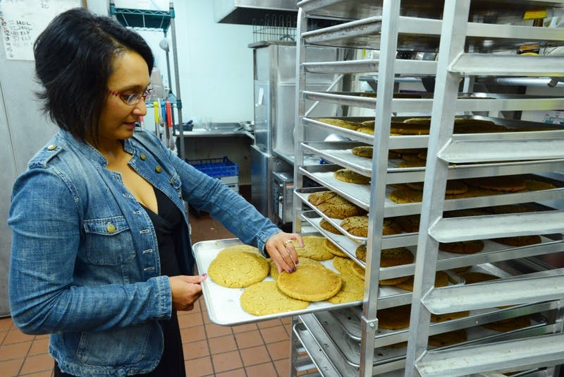 T-Rex Cookie Owner Tina Rexing takes a fresh tray of cookies off the cooling rack on Saturday, June 9. The arts and architecture building that T-Rex Cookie operates in will be replaced by new apartments and retail space in 2018.