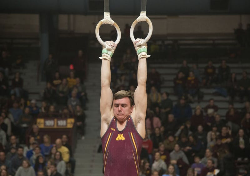 Sophomore Henry Meeker competes in the still rings at the Maturi Pavilion on Saturday, Jan. 26.