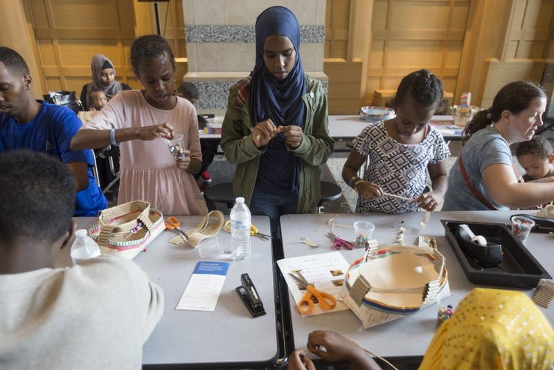 "Nasram Qasim, left, Nasra Qasim and Hana Qasim weave traditional Somali baskets at the History Center's new ""Somalis + Minnesota"" exhibit on Saturday, June 23 in Saint Paul. The baskets are made to hold household items."