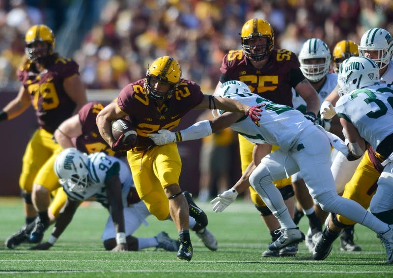 Running back Shannon Brooks pushes an Ohio defenseman aside on his way to score a touchdown at the Homecoming game in TCF Bank Stadium on Saturday where the Gophers won 27-24.