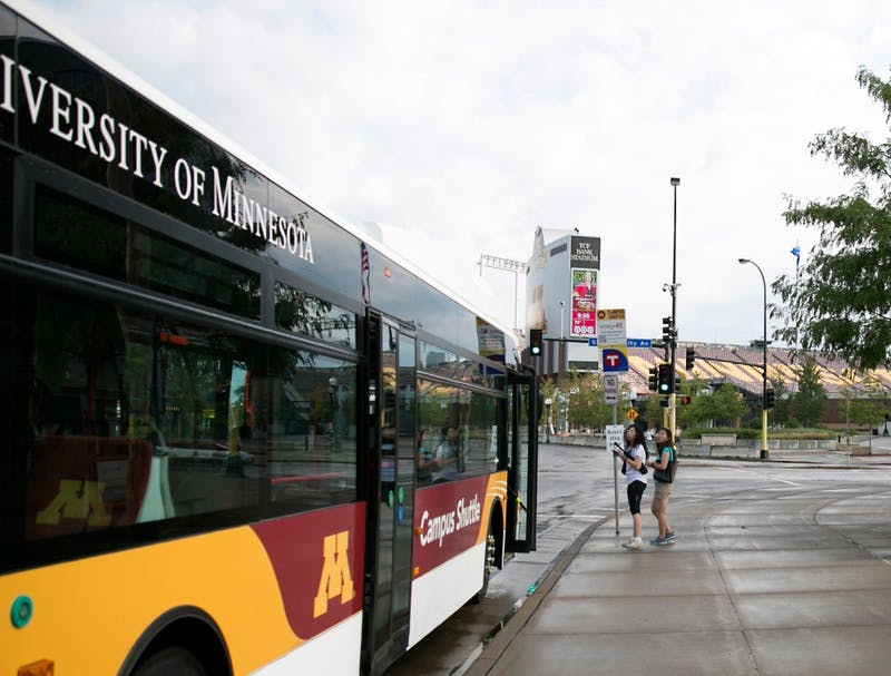 Pedestrians board a campus shuttle at the corner of University Ave SE & SE Oak St on Sunday. The new bus stop near TCF Bank Stadium is one of many new stops the University has implemented for the Fall of 2015.