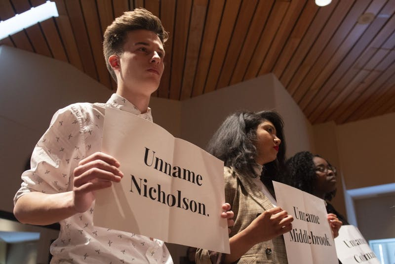 Student demonstrators hold up signs in protest of the Board of Regents' position on building renaming during the special session on Friday, April 26. The board voted against the renaming of four buildings on campus after more than a year of community discussion on the issue.