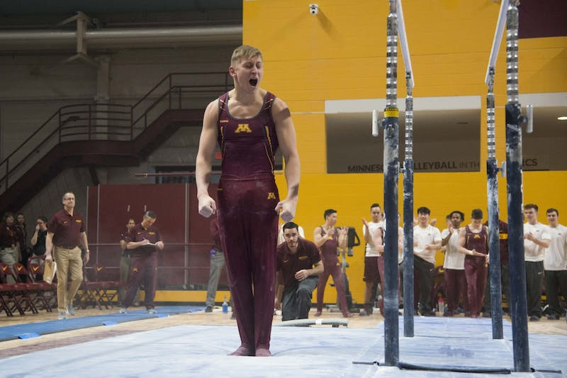 Senior Timmy Kutyla competes in the parallel bars at the Maturi Pavilion on Saturday, Jan. 26, 2019.