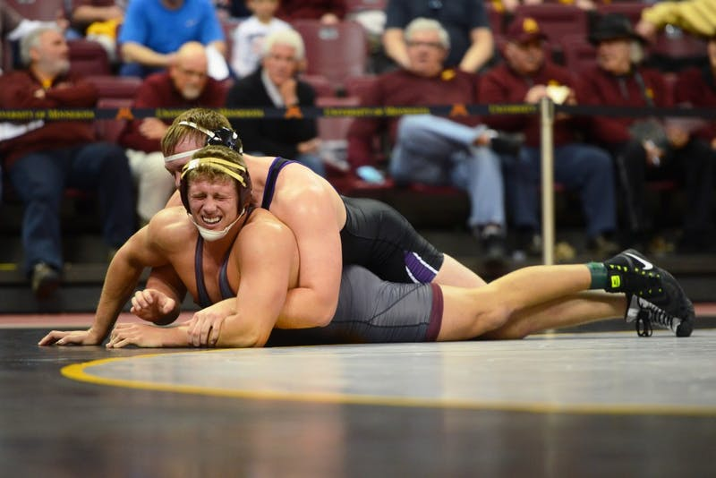 Sophomore heavyweight wrestler Rylee Streifel matches a Northwestern wrestler during the match on Sunday, Jan. 28, at Maturi Pavilion.