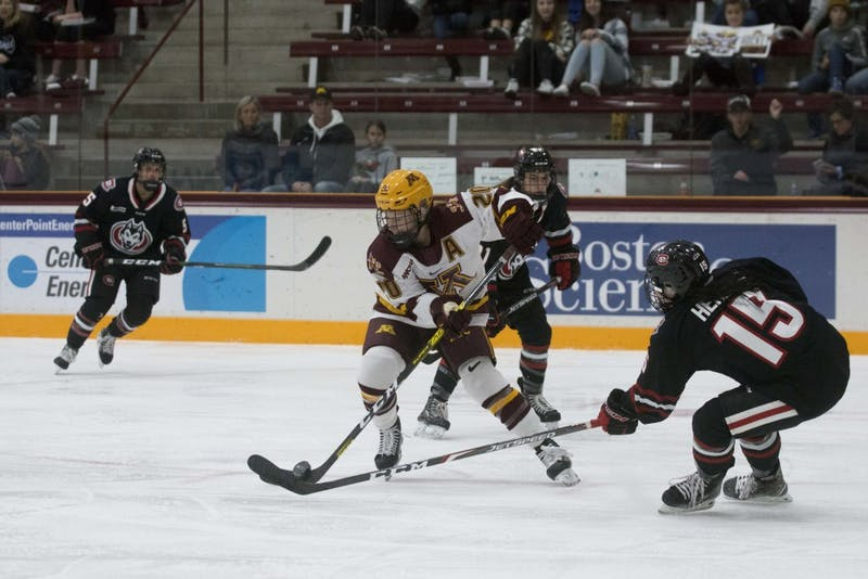 Forward Alex Woken fights for the puck at Ridder Arena on Saturday, Oct. 19. The Gophers defeated St. Cloud State 3-0.