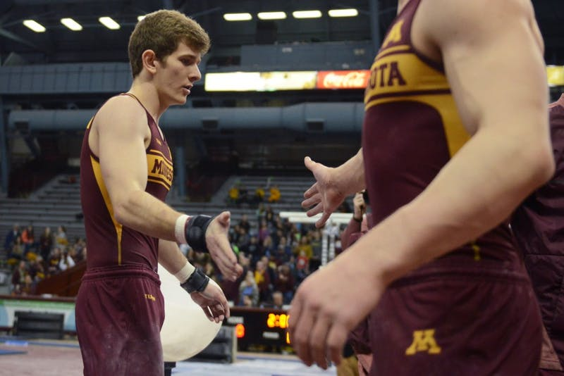 Luke Aldrich high-fives a teammate after competing on the pommel horse on Sunday, March 18.