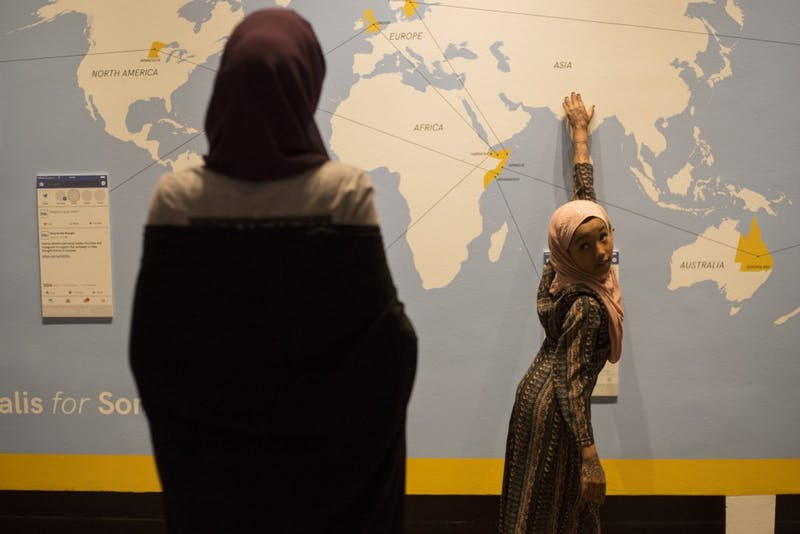 """Lima Ahmad, 8, asks her older sister about different countries on a map at the History Center's new """"Somalis + Minnesota"""" exhibit on Saturday, June 23 in Saint Paul."""