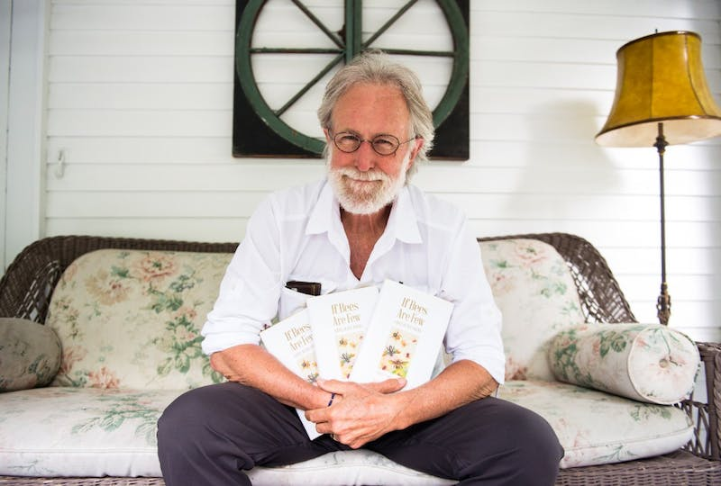 """Former Star Tribune editorialist Jim Lenfestey poses with copies of his anthology of bee-related poems at his home on Monday. The anthology, titled """"If Bees Are Few"""", was published with the University of Minnesota Press, and all proceeds will be donated to the University's Bee Lab."""