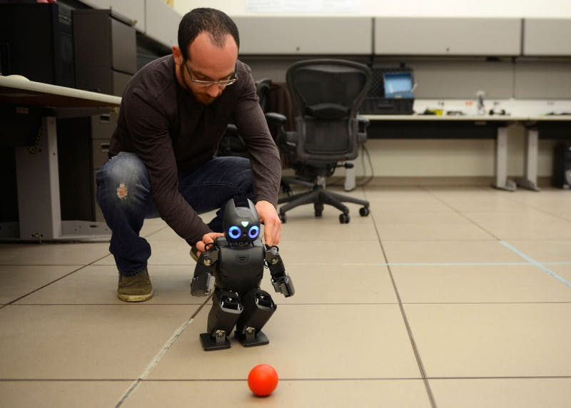 Ph.D. candidate Dimitris Zermas plays soccer with Darwin the Humanoid Research Robot in Walter Library on Friday, April 3rd.