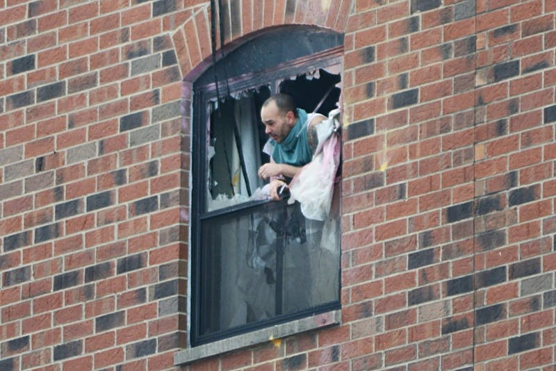Rashad Bowman, 43, pokes his head out the sixth floor window at 11:40 a.m. Tuesday after police fired gas into a sixth floor room at the Graduate Hotel.