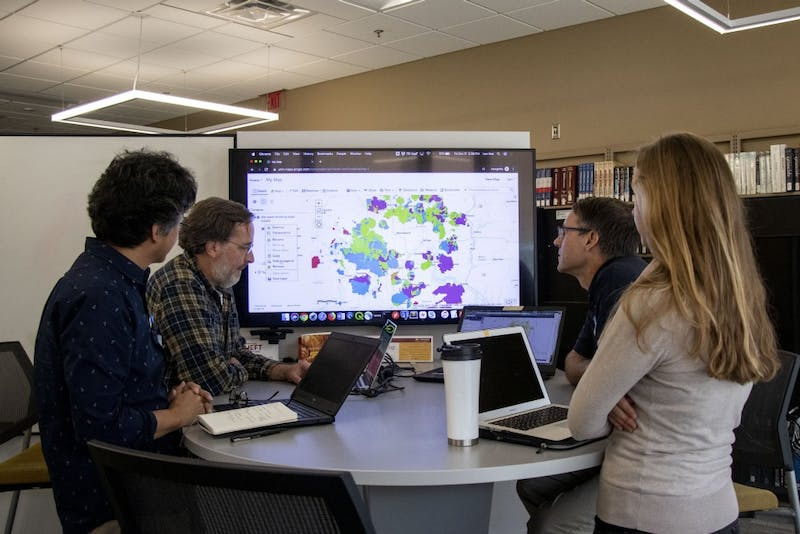 From left, Kyungsoo Yoo, Len Kne, Darrell Gerber and Melinda Kernile explore the mapping of data regarding drinking water supply with ArcGIS in the Collaborative Research Studio in Wilson Library on Friday, Oct. 11.