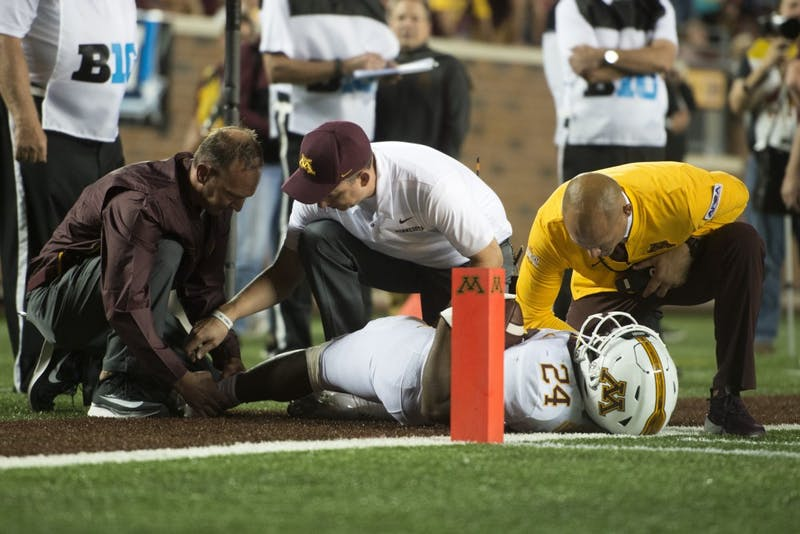 Running back Mohamed Ibrahim speaks with Head coach P.J. Fleck following an injury at TCF Bank Stadium on Thursday, Aug. 30.