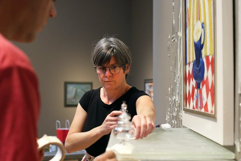Artist Beth Lipman puts the finishing touches on her new work in Weisman Art Museum on Friday, Sept. 29.  The glass sculpture's height reaches more than halfway up the museum's wall.