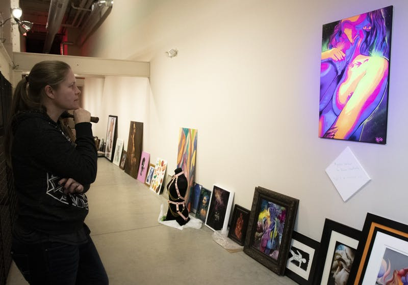 Angel Hawari evaluates the placement of a painting during setup for Safeword: An Erotic Art Show at the A-Mill Underground Museum on Saturday, Feb. 8.