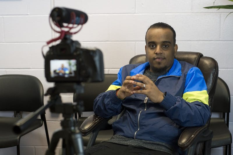 "Filmmaker Sisco Omar poses for portrait before filming an interview on Wednesday, May 1 at the Bryan Coyle Center. Omar says that, ""Everyone has a story to tell,"" and believes that the stories from the Cedar-Riverside community are best told from the perspective of the people who live there."
